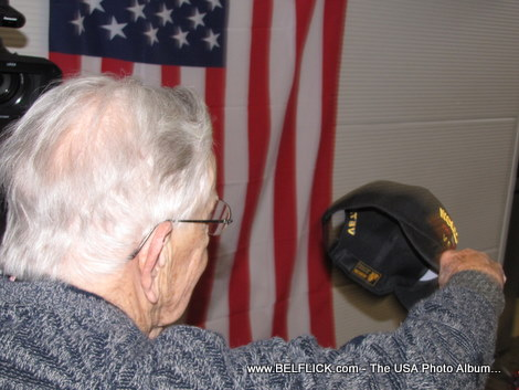 Old World War II veteran takes off his hat to salute the American flag. Or did he? LOL...
