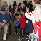 A World War II veteran sits on a wheelchair while an adoring crowd cheers for him